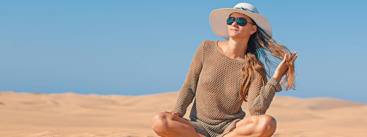 Woman-Sunglasses-Hat-Sitting-Beach-1280x480